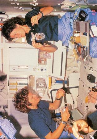 Sally (na górze) i Kathy Sullivan spożywają wspólny posiłek na pokładzie wahadłowca Challenger podczas drugiej misji Ride. Zdjęcie jest wykonane we właściwej orientacji. W stanie nieważkości astronautki mogły jeść siedząc na boku, do góry nogami i w każdej dowolnej pozycji/ Credits: SRS