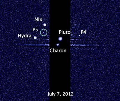 Pluton w otoczeniu księżyców. Zaznaczony nowo odkryty satelita P5/ Credits: NASA, ESA