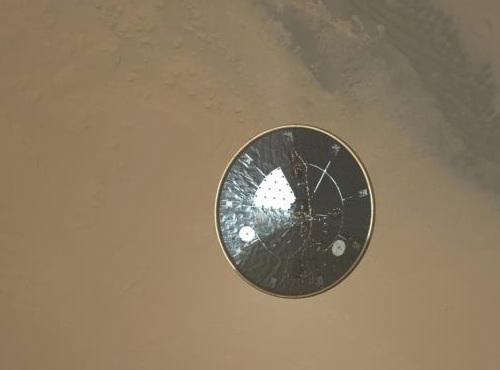Wycinek zdjęcia w wysokiej rozdzielczości pochodzący z kamery MARDI i przedstawiający opadającą osłonę termiczną lądownika (NASA/JPL-Caltech/Malin Space Science Systems)
