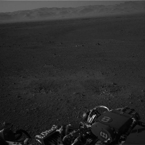 Powierzchnia Marsa, usiana niewielkimi fragmentami skał. W oddali widoczna krawęź krateru Gale. Zdjęcie pochodzi z jednej z dwóch prawych kamer Navcam (NASA/JPL-Caltech)