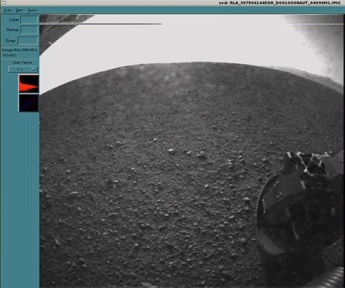 Obraz w większej rozdzielczości z jednej z kamer HazCam po odrzuceniu jej pokrywy chroniącej przed pyłem. W oddali widać prawdopodobnie krawędź krateru (NASA TV)