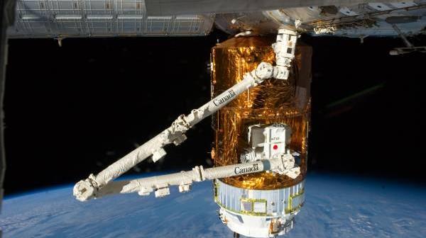 Japoński statek transportowy zacumowany do portu modułu Harmony. Na zdjęciu widoczne ramię Stacji ISS (SSRMS, Canadarm2) podłączone do palety ładunkowej znajdującej się w luku nieciśnieniowym statku / Credits: NASA