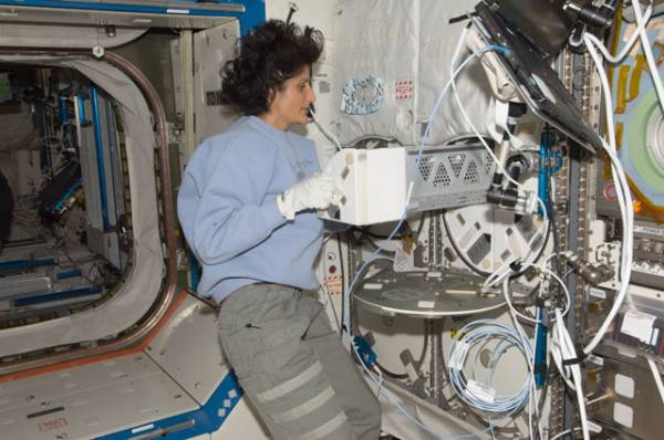 Astronautka NASA Sunita Williams umieszczająca próbki biologiczne w zamrażarce MELFI-2 / Credits: NASA