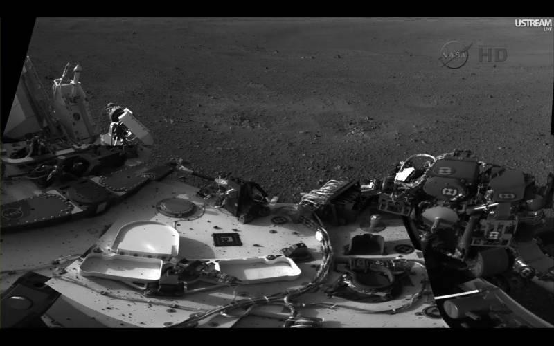 Górna strona łazika Curiosity. Widoczne są drobiny gruntu, które zostały podniesione z powierzchni w efekcie działania silników rakietowych platformy SkyCrane. Naukowcy będą zwracali uwagę na położenie tych drobin w czasie jazdy łazika (m.in. w czasie pochylenia) / Credits: NASA