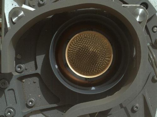 Otwór o szerokości 3,5 cm prowadzący do wnętrza instrumentu CheMin. Widoczne sito umieszczone jest na głębokości niecałych 6 cm. Poniżej znajduje się komora, w której próbki będą prześwietlane promieniami rentgena (badania chemiczne oraz mineralogiczne). Zdjęcie wykonane zostało przez kamerę MAHLI z wysokości około 20 cm nad otworem / Credits: NASA/JPL-Caltech/MSSS