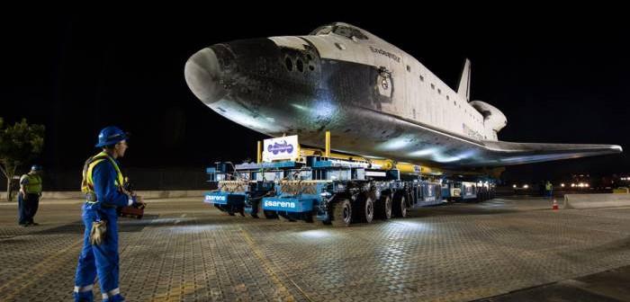 Prom kosmiczny Endeavour w drodze do nowego domu - Kalifornijskiego Centrum Naukowego. Człowiek na pierwszym planie odpowiada za kontrolę nad maszyną transportującą wahadłowiec / Credits: NASA/Bill Ingalls