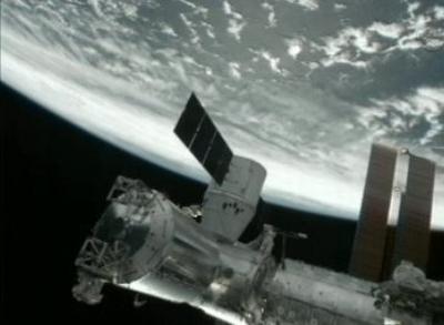 Statek Dragon-1 (z ogniwem fotowoltaicznym na tle Ziemi) przyłączony do stacji ISS / Credits: NASA TV
