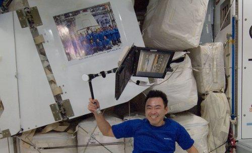 Japończyk Aki Hoshide obok plakatu przesłanego w kapsule Dragon. Zdjęcie z 14 października 2012 / Credits - NASA