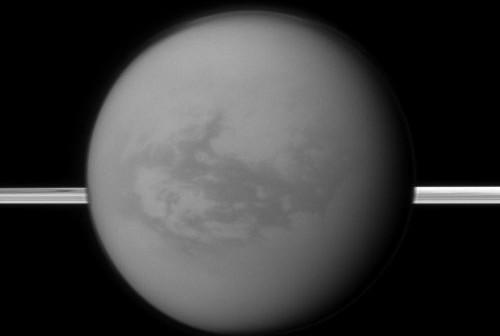 Tytan. W tle pierścienie Saturna. W pobliżu równika księżyca znajduje się ciemniejszy obszar – nazwany Shangri-La, gdzie odkryto metanowe jezioro. Credit: NASA/JPL-Caltech/Space Science Institute