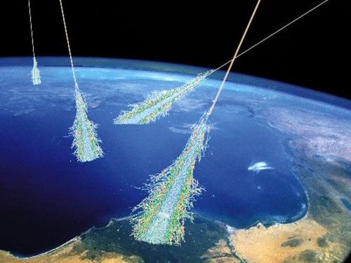 Ilustracja: wysokoenergetyczne cząstki promieniowania kosmicznego w kolizjach w naszej atmosferze tworzą deszcze promieniowania wtórnego, z którego część dociera do powierzchni Ziemi, jednakże nie stanowi ono dla nas istotnego zagrożenia (dawka promieniowania jest bardzo mała). Credits: Simon Swordy (U. Chicago), NASA