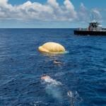 Odzyskiwanie kapsuły LDSL - nurkowie podpływają do kapsuły / Credits: NASA