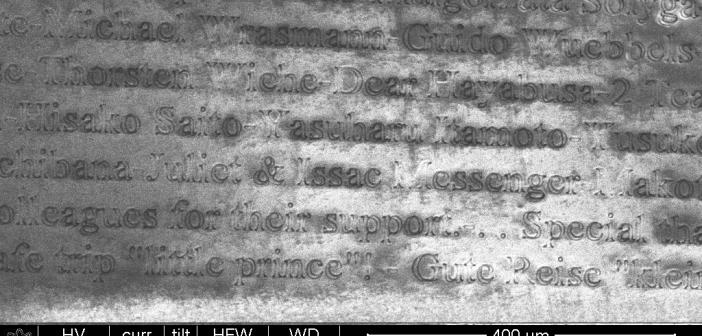 """Imiona i nazwiska """"fanów"""" misji naniesione na metalowe folie na MASCOT - zdjęcie z mikroskopu elektronowego"""