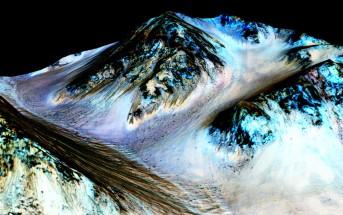 Ciemne, 100-metrowe smugi wskazują na występowanie płynnej wody na Marsie. Naukowcy odkryli uwodnione sole w ciemnych smugach. Niebieskie obszary to minerał piroksen, nie związany bezpośrednio z potokami solanki. Credits: NASA/JPL/University of Arizona