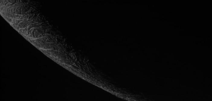 Fragment krawędzi Enceladusa z atmosferą Saturna w tle / Źródło: NASA