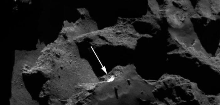 Zdjęcie klifu Aswan wykonane 26 grudnia 2015 roku z odległości 77,05 km od jądra komety 67P. Biała strzałka wskazuje jasny klif Aswan z odkrytym lodem wodnym. Źródło: ESA/Rosetta/MPS for OSIRIS Team MPS/UPD/LAM/IAA/SSO/INTA//UPM/DASP/IDA