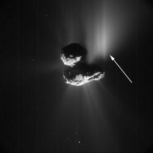 Zdjęcie z kamery NavCam wykonane 10 lipca 2015 roku z odległości 156,58 km od jądra 67P. Biała strzałka wskazuje emisję pyłu spowodowaną osunięciem się klifu Aswan. Źródło: ESA/Rosetta/NavCam