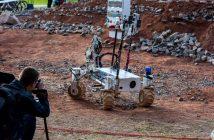 Polski łazik z nietypowymi, obrotowymi kołami wykonanymi w technologii druku 3D z wypełnieniem w formie plastra miodu, co czyni je lekkimi oraz bardzo twardymi - robot zmierza do tablicy z przełącznikami podczas jednej z konkurencji / Credits - Marcin Szustak