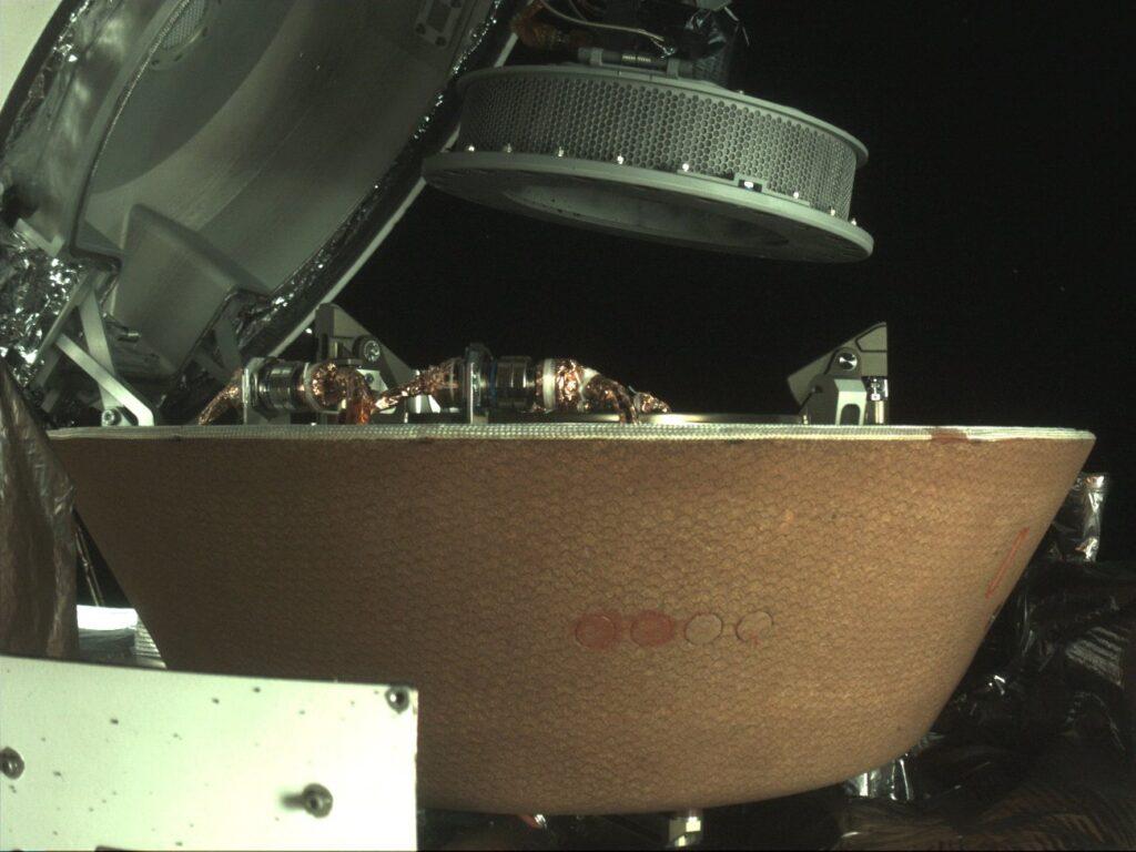 Końcowe etapy wprowadzania zasobnika z próbkami planetoidy Bennu do wnętrza kapsuły powrotnej / Credits - NASA